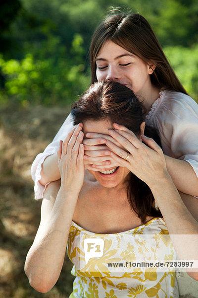 Tochter bedeckt die Augen der Mutter
