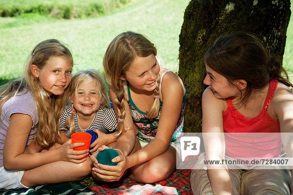 Four children sitting on picnic blanket