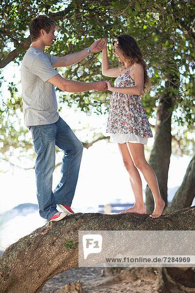 Paar,  das sich gegenseitig an einem Baumzweig hält.