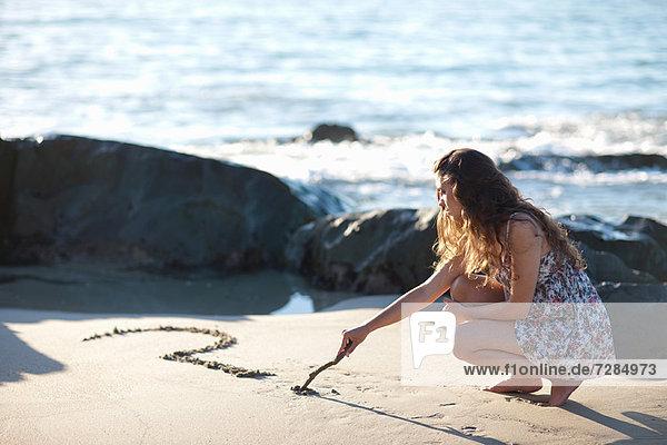 Frau zeichnet Fragezeichen im Sand
