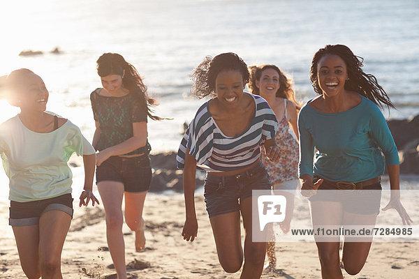 Women running together on beach