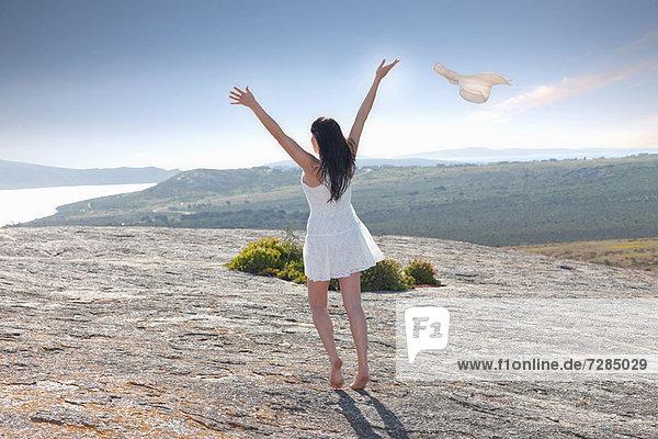 Frau spielt auf einer Felsformation