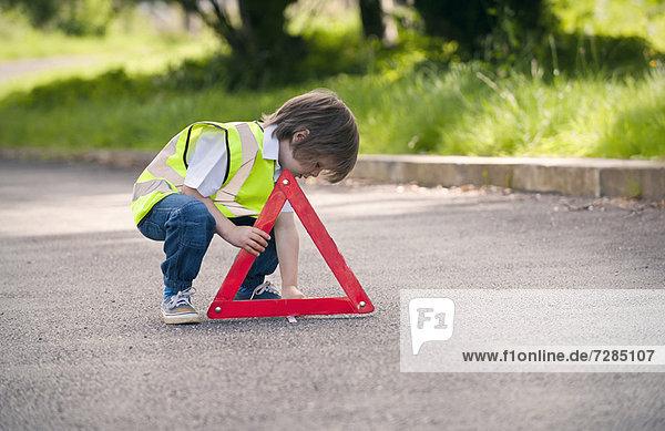 Junge spielt Verkehrsarbeiter auf der Landstraße