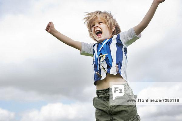 Junge mit Medaillenjubel im Freien