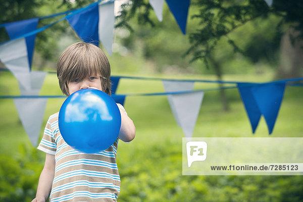 Junge bläst Ballon im Freien auf
