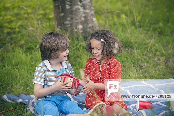 Mädchen schenken beim Geburtstagspicknick