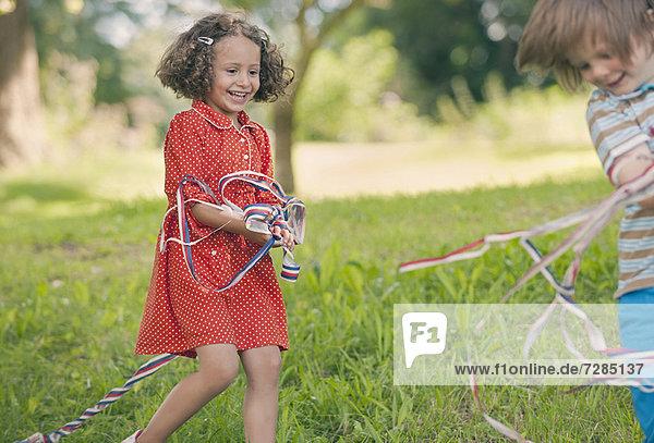Kinder spielen mit Bändern im Freien