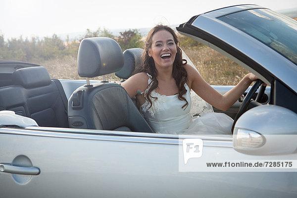 Neuvermählte Braut im Cabrio sitzend