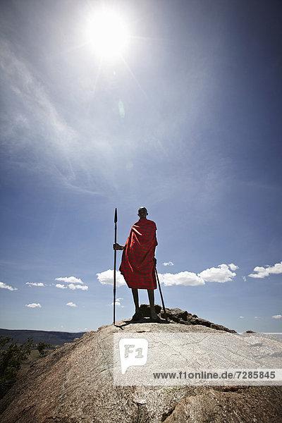 Maasai-Mann auf dem Felsen stehend