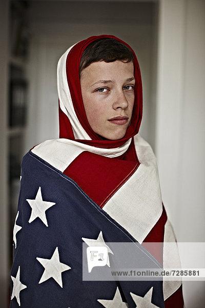 Junge mit amerikanischer Flagge im Haus