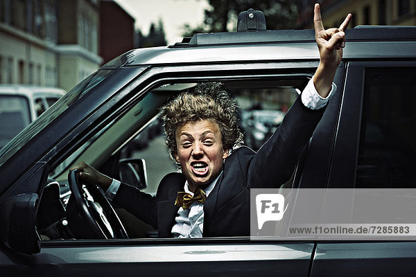 Teenage boy cheering while driving