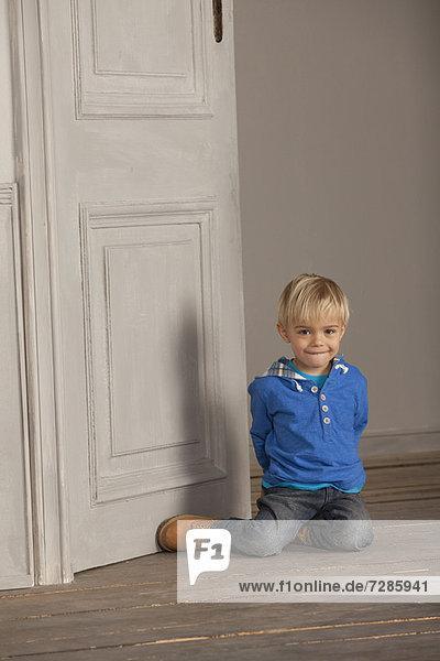 Boy sitting on wooden floor