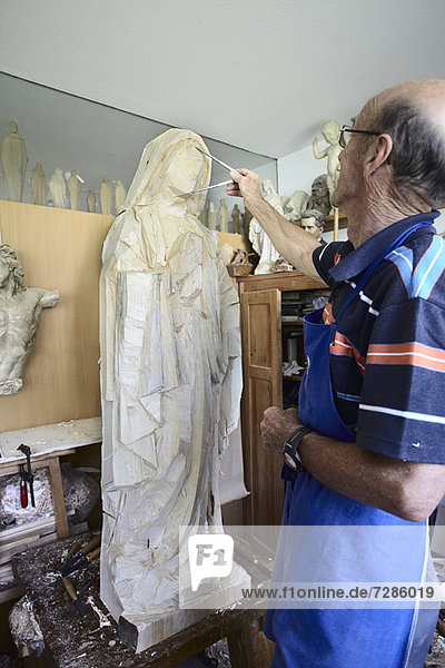 Bildhauer  der die Holzfigur bewundert
