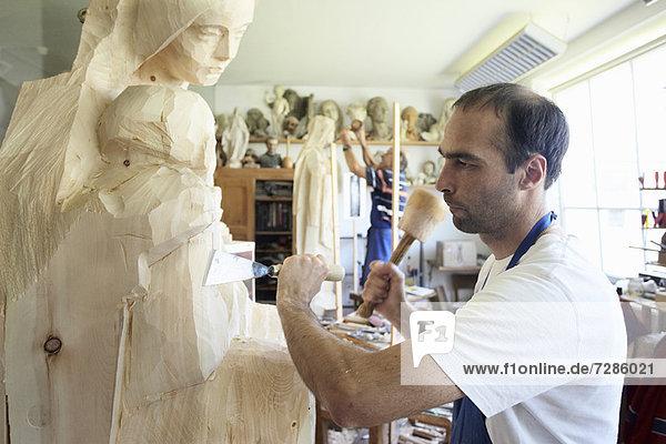 Bildhauer meißelnde Figur aus Holz