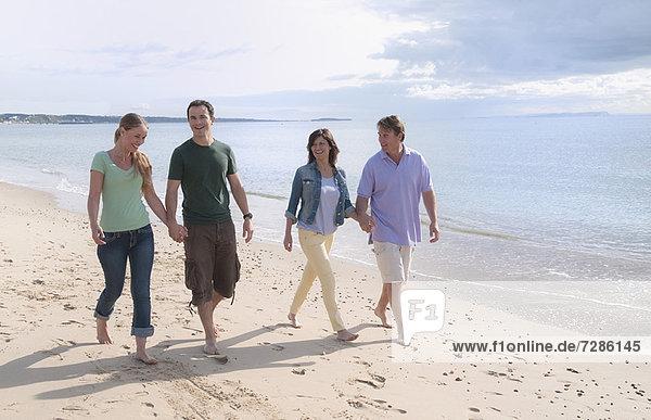 Paare halten sich am Strand an den Händen