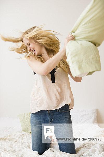 Frau  werfen  kniend  Bett  Kopfkissen  jung