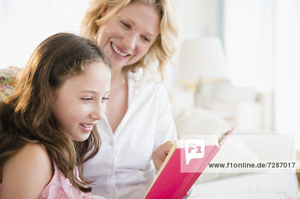 Mother and daughter (8-9 years) reading book