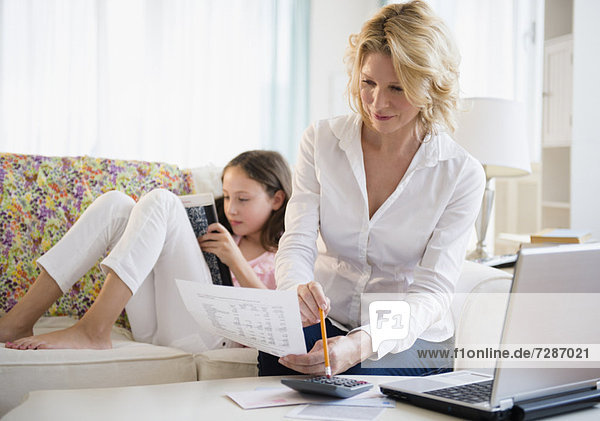 Mother paying bills via internet while daughter (8-9 years) reading book on sofa