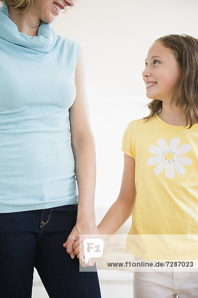 Mother and daughter (8-9 years) holding hands