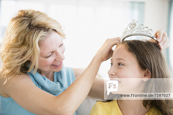 Mother putting tiara on daughter's (8-9 years) head