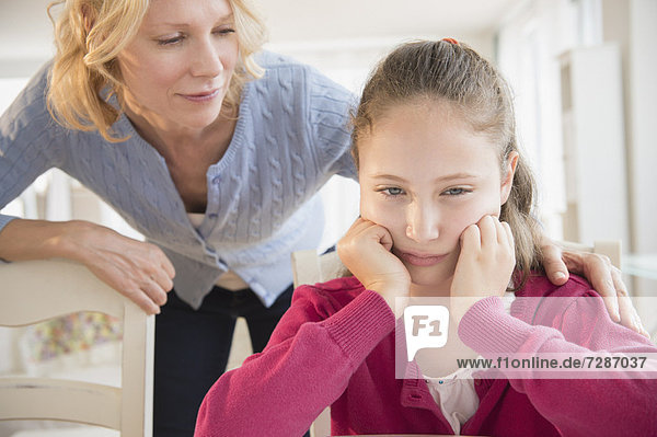 Mother consoling sad daughter (8-9 years)