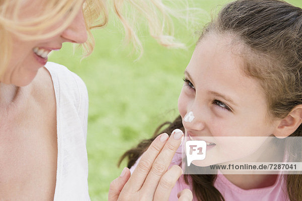 Mother applying moisturizer on daughter's (8-9 years) nose