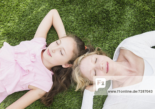 Mother and daughter (8-9 years) lying on grass