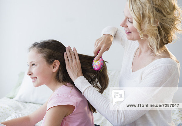 Mother combing daughter's (8-9 years) hair