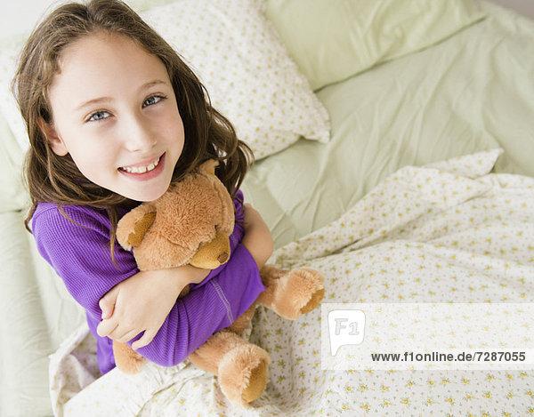 Portrait of girl (8-9) embracing teddy bear
