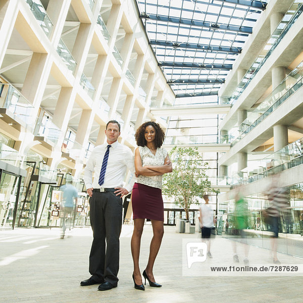 Portrait of man and woman standing in modern building