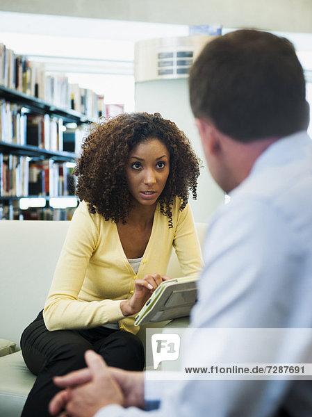 Mann und Frau unterhalten sich in Bibliothek