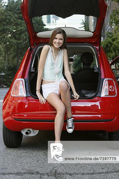 sitzend  Frau  Auto  offen  Kofferraum  jung