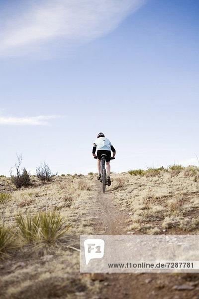 Rear view of man biking on trial
