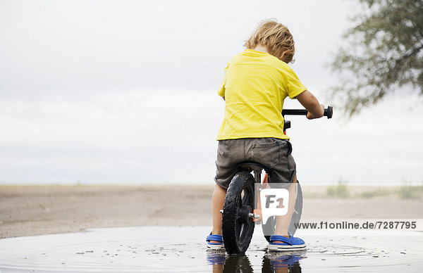 Toddler boy (2-3) riding bicycle in puddle