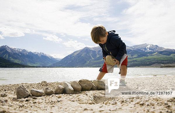 Boy (2-3) with rocks on beach