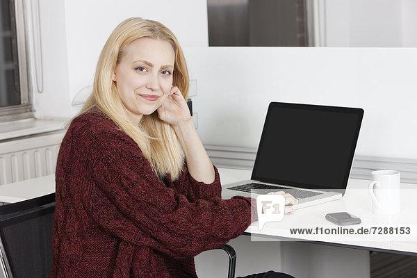 sitzend  Portrait  Geschäftsfrau  Schreibtisch  Fröhlichkeit  Notebook  Büro  jung