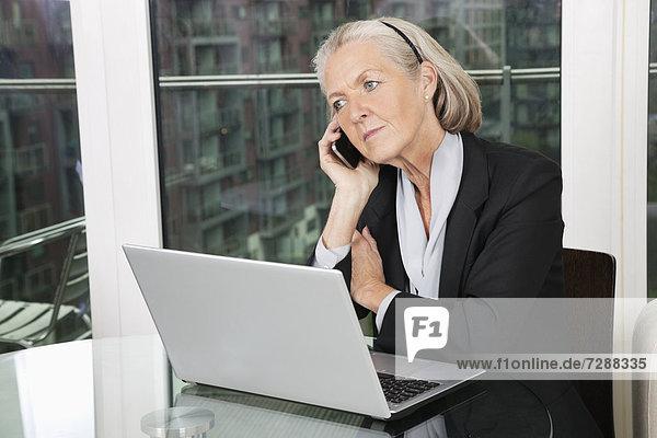 Handy  sitzend  Senior  Senioren  benutzen  Geschäftsfrau  Notebook  Tisch