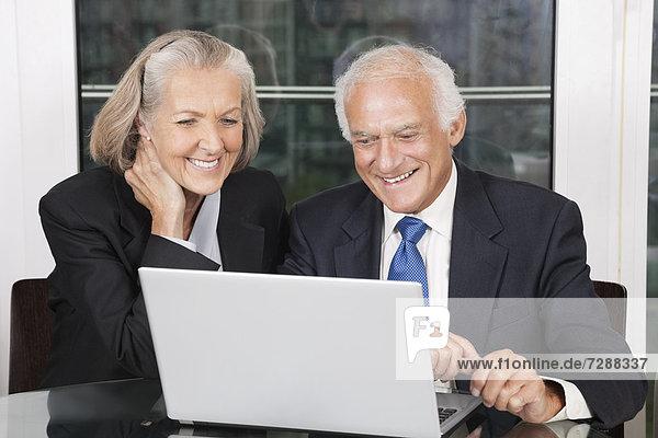 sitzend  Senior  Senioren  Fröhlichkeit  sehen  Notebook  weiß  Tisch  Business