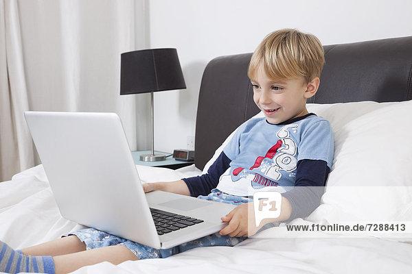 benutzen Europäer Computer Notebook lächeln Junge - Person Bett