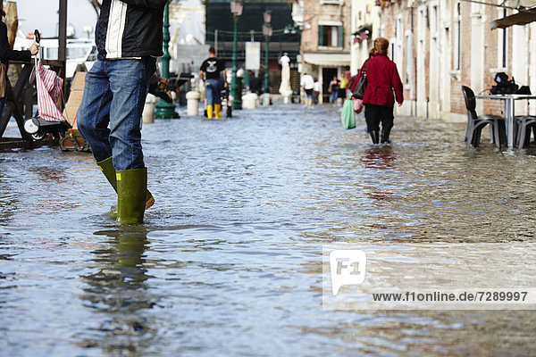 Pedestrians in high tide in Venice  Italy