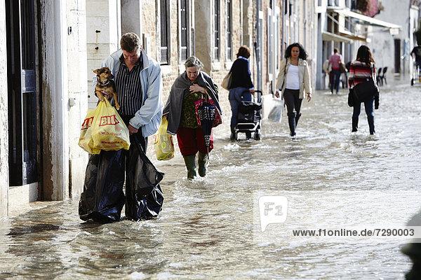 Fußgänger im Hochwasser in Venedig  Italien
