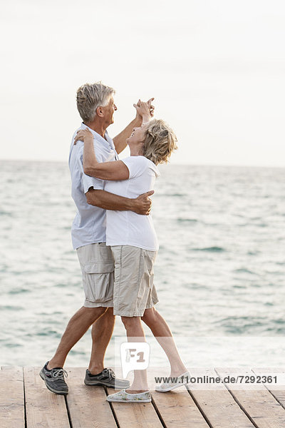Spain  Senior couple dancing on jetty at the sea Spain, Senior couple dancing on jetty at the sea