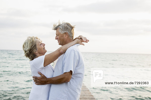 Spain  Senior couple embracing at the sea