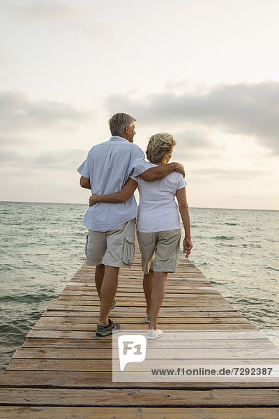 Spain  Senior couple standing on jetty at the sea