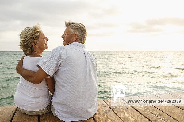 Spanien  Seniorenpaar umarmt am Meer