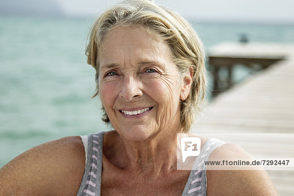 Spain  Senior woman sitting on jetty at the sea  smiling  portrait