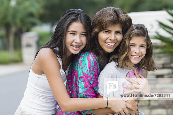 Smiling Hispanic mother and daughters