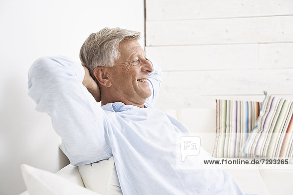 Spain  Senior man relaxing on couch  smiling