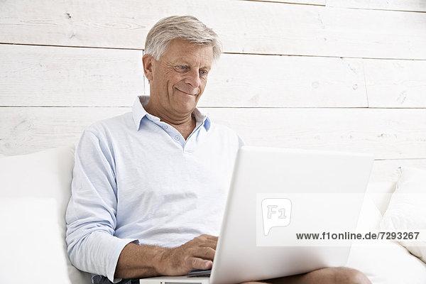 Spain  Senior man checking emails on laptop  smiling