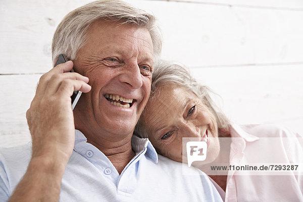 Spanien  Seniorenpaar im Gespräch mit dem Handy  lächelnd